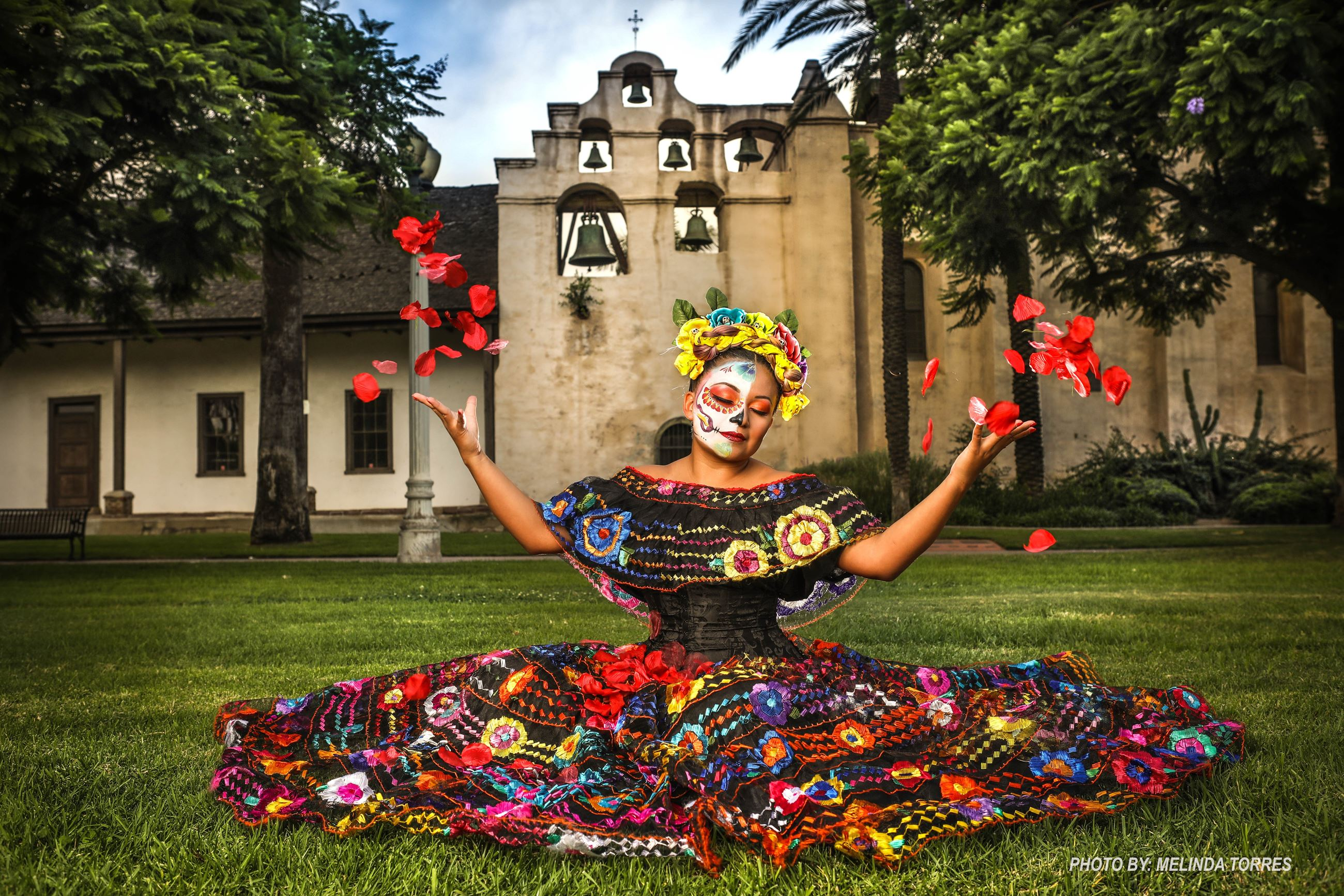 Woman wearing sugar skull make up and traditional dress throwing rose petals in the air