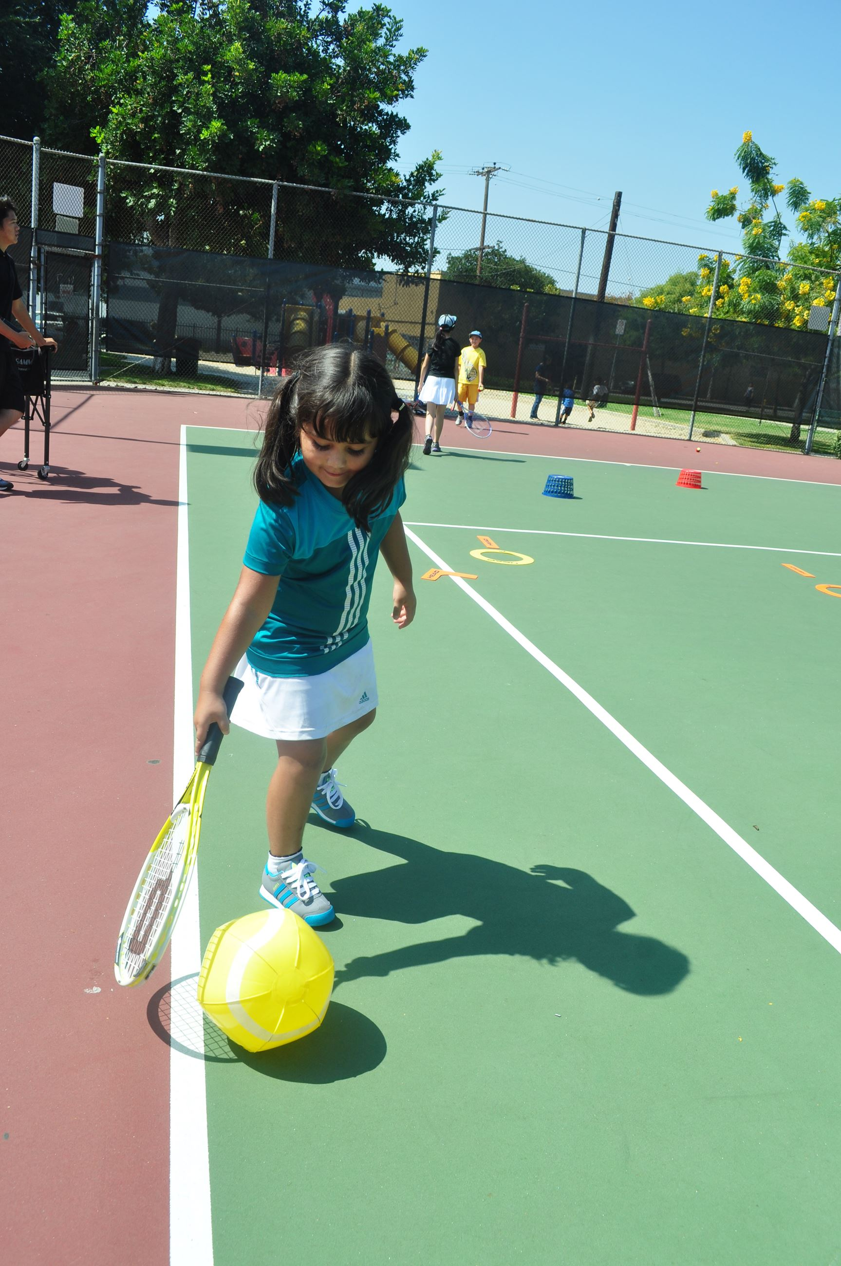 Little girl playing on a tennis court.